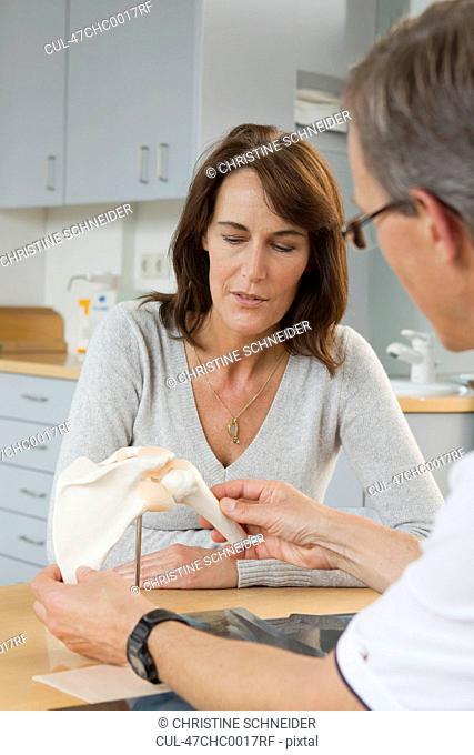 Doctor showing patient model of bones