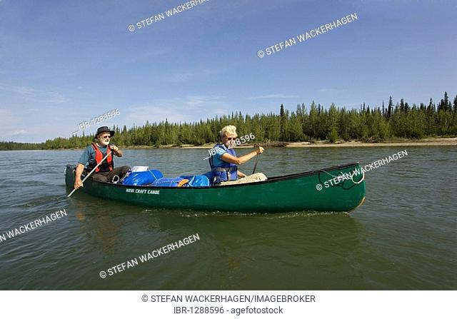 Older couple, man and woman paddling a canoe, canoeing, upper Liard River, Yukon Territory, Canada