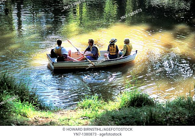 Romantic image of four people in a rowing boat on a secluded location on the river