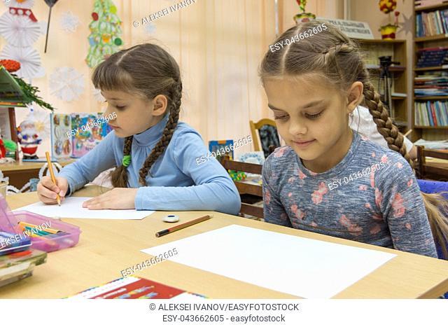 Schoolgirls at their desks in drawing class