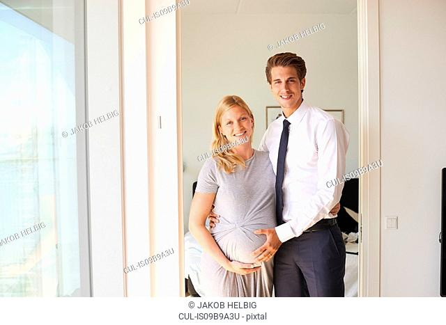Portrait of pregnant couple with hands on her stomach in apartment