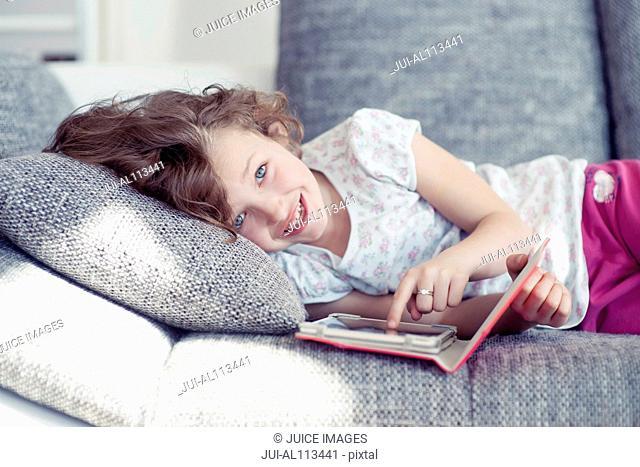 Young girl using digital tablet on sofa