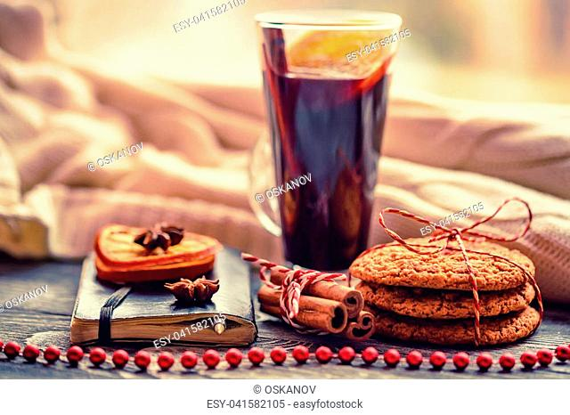 New Year winter still life: warm woolen knitting, hot mulled wine, cinnamon, Christmas cookies and orange. Hygge style. Cozy winter home morning holiday