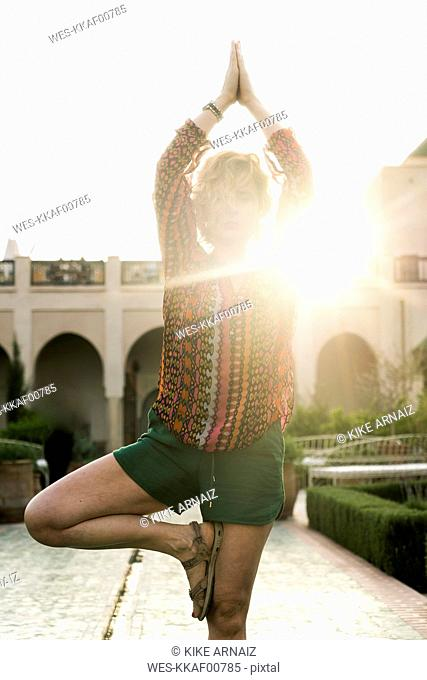 Morocco, Marrakesh, tourist doing yoga in courtyard