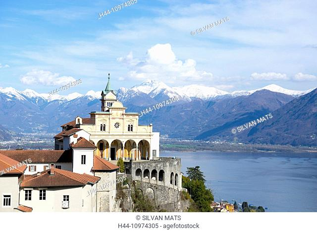 Church madonna del sasso in locarno on the mountain with an alpine lake and snow-capped mountain in background with blue sky and clouds in Ticino, Switzerland