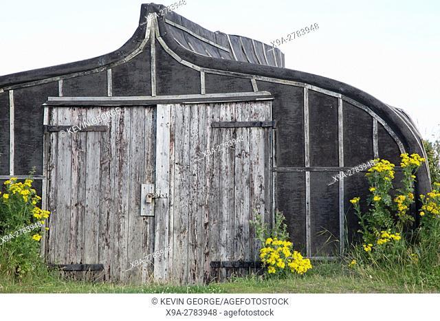 Upturned Boat used as Shed with Traditional House, Lindisfarne; Holy Island; Northumberland; England; UK