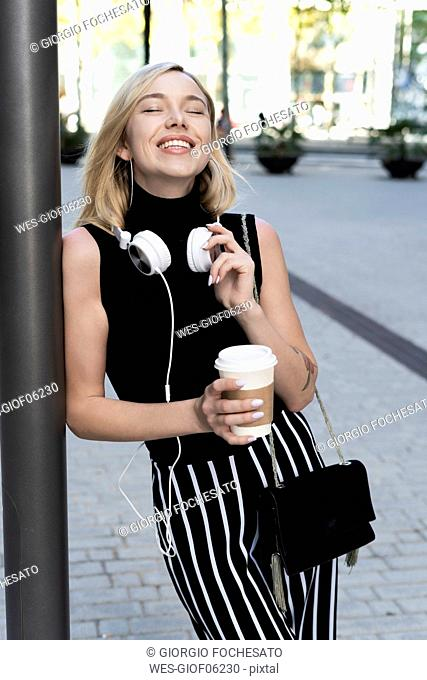 Portrait of happy blond woman with coffee to go, shoulder bag and headphones