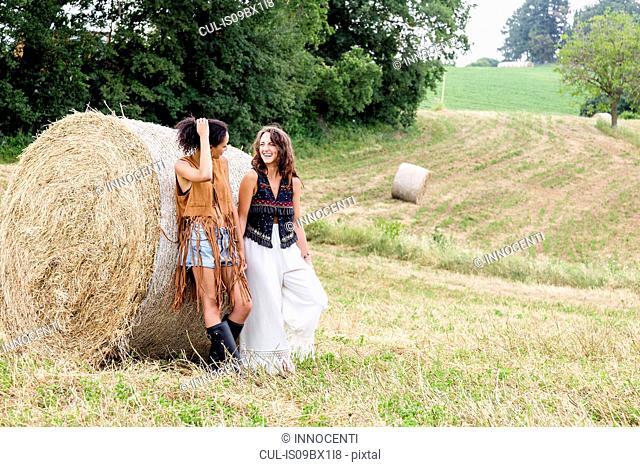 Friends in field of hay bales, Città della Pieve, Umbria, Italy