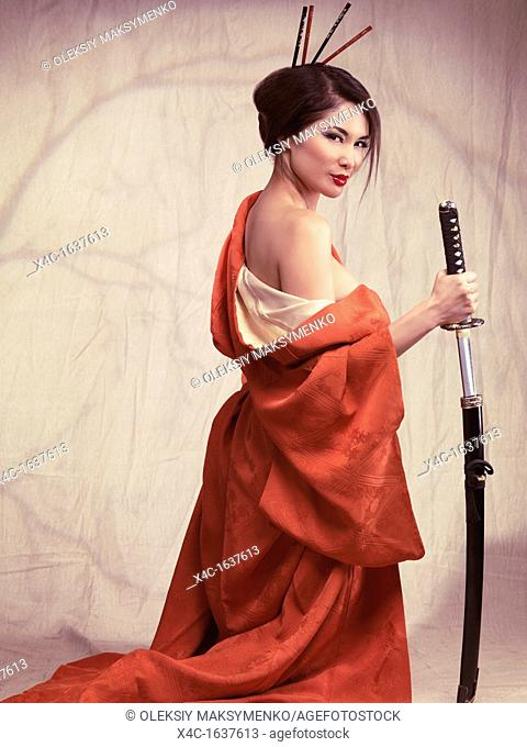 Beautiful sexy asian woman in red kimono unsheathing katana sword