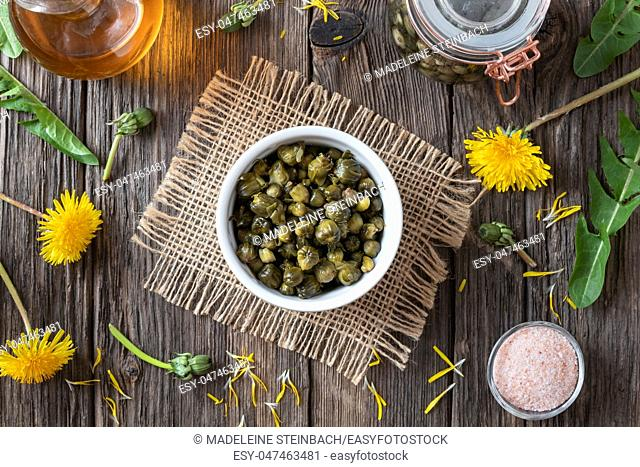 False capers made from young dandelion buds in a bowl, top view