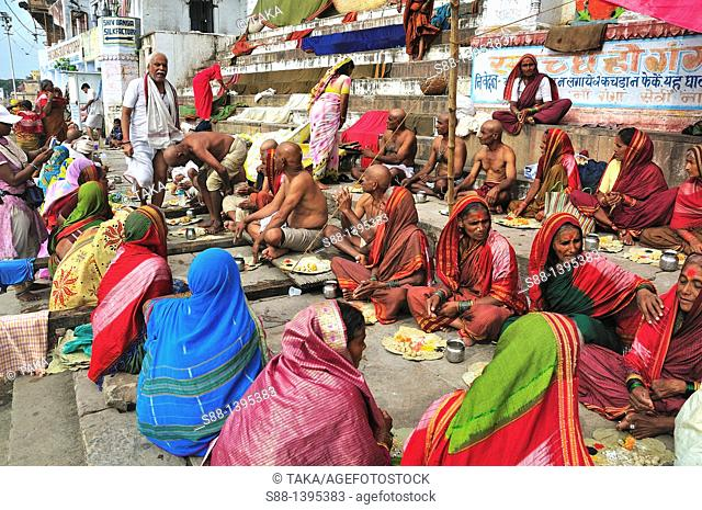 Grope of pilgrims praying at the ghat by the Ganges river