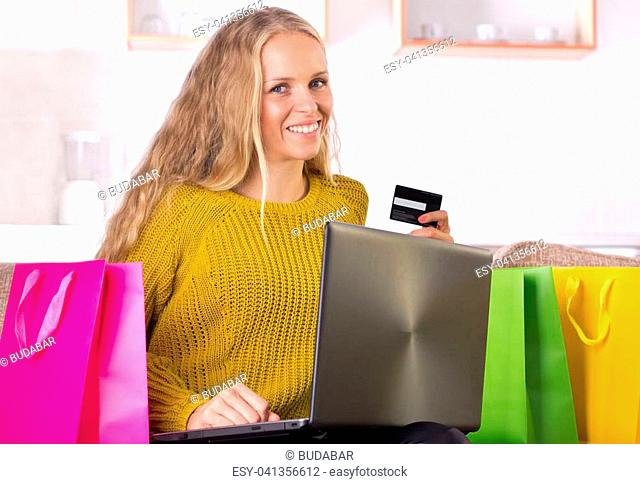 Happy young woman sitting on sofa at home with shopping bags around and holding laptop and credit card. Online buying concept