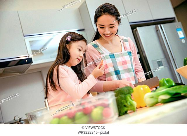 The young mother and her daughter in the kitchen