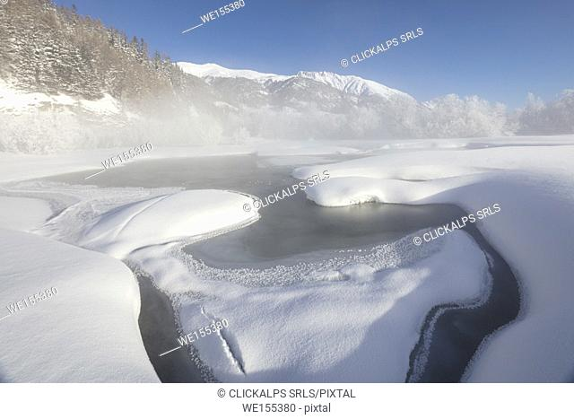 Mist on the snowy landscape and frozen river Inn Celerina Maloja Canton of Graubunden Engadine Switzerland Europe