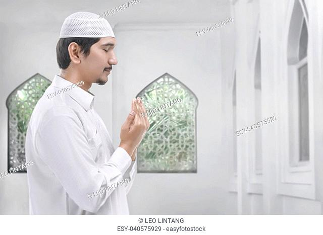 Side view of asian muslim man praying inside the mosque