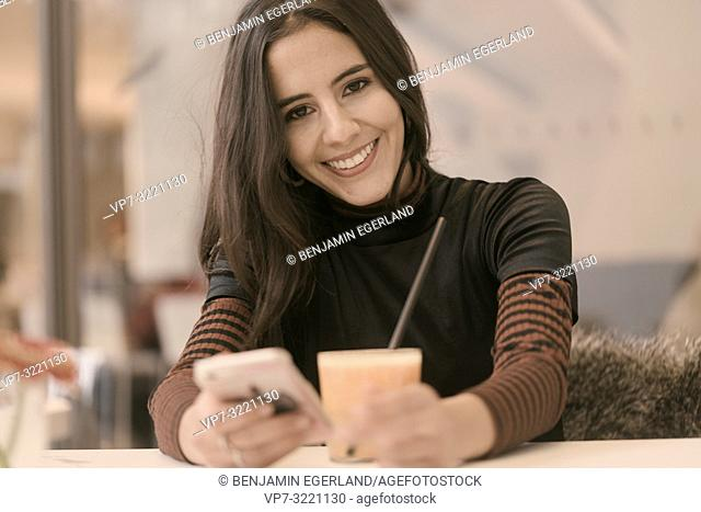 portrait of happy smiling woman using phone while taking a break with healthy juice glass at table in café, in Munich, Germany