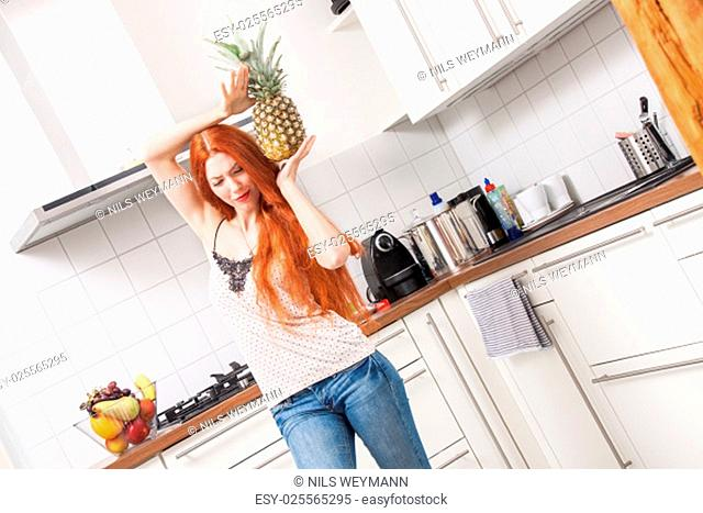 sing happy young woman in the kitchen with a pineapple in hand at
