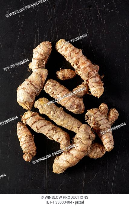 Turmeric roots on black background
