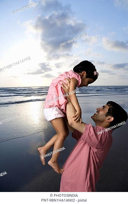 Side profile of a mid adult man playing with his daughter on the beach