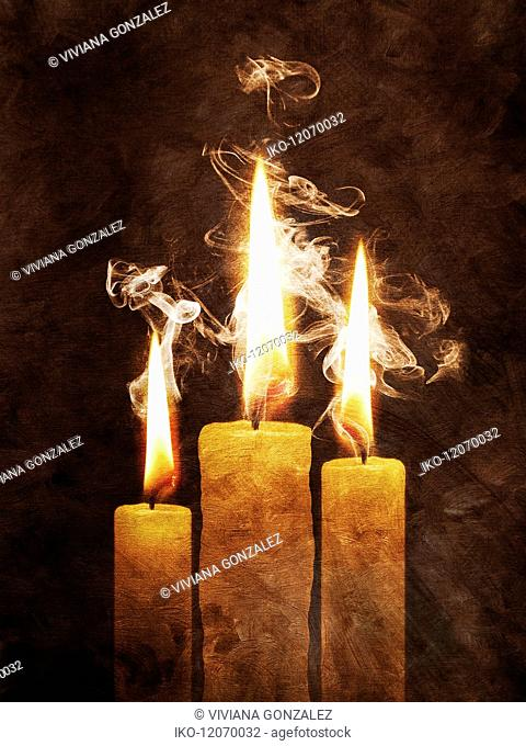 Smoke rising and swirling from lit candles