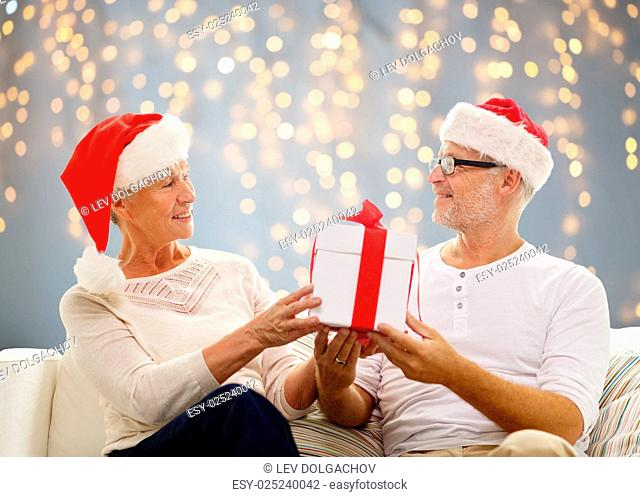family, holidays, christmas, age and people concept - happy senior couple in santa helper hats with gift box over lights background