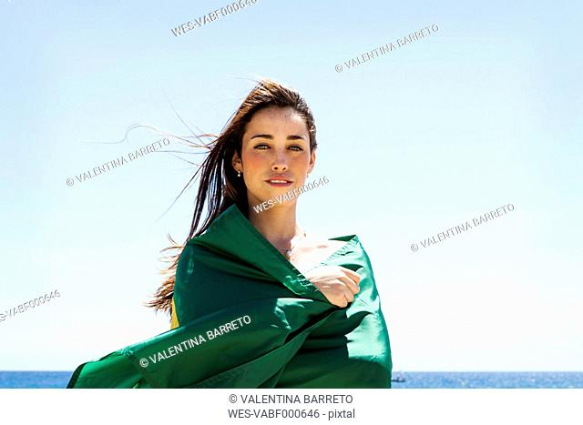 Young brunette woman playing with Brazilian flag at the beach