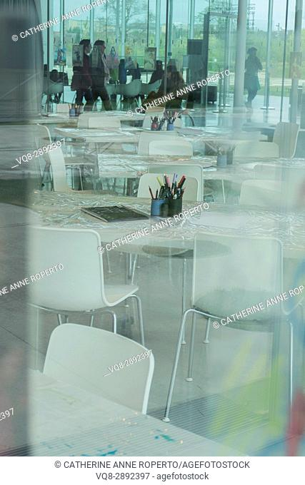 Reflective table coverings and art materials through glass in activity area of contemporary curved glass space with students, Lens, France