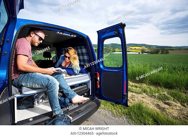 A quick rest stop along the road, a couple sits in the back of a camper van with the doors open; Czech Republic