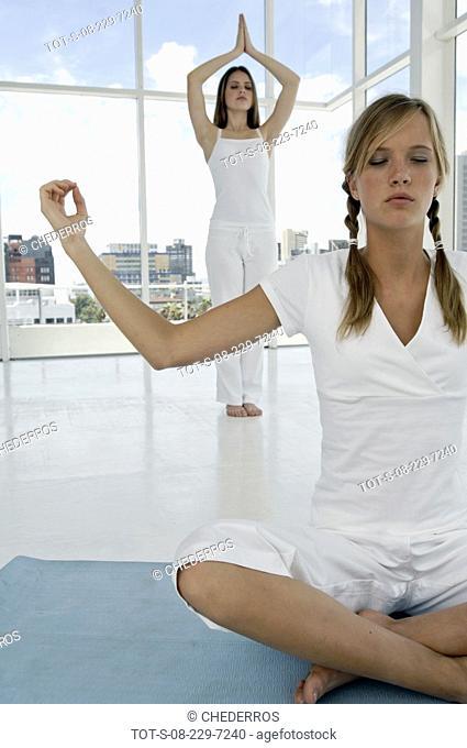 Two teenage girls practicing yoga