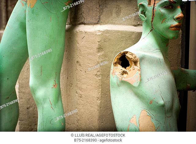 Legs and bust of an old green painted mannequin, leaning on a wall in Barcelona, Spain, Europe