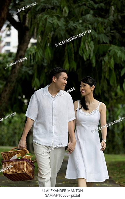 Man and woman in park smiling at each other
