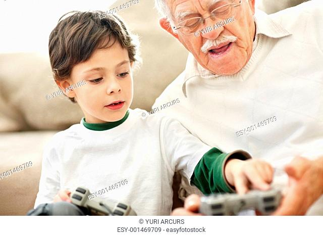 Portrait of little boy helping his grandfather while playing video game at home