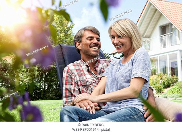 Happy mature couple on deck chair in garden