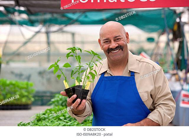 Mature man holding pot plant in garden centre, smiling