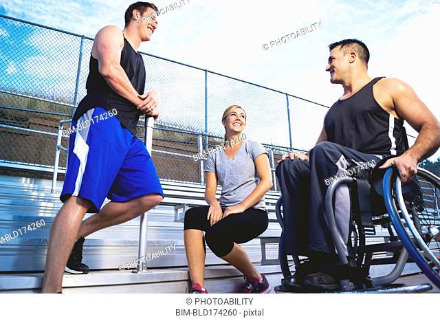 Paraplegic athlete in wheelchair with friends on bleachers
