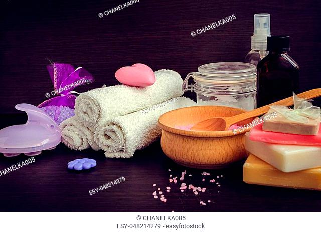 Composition of spa treatment on the dark wooden table. Spa and wellness setting with natural soap, sea salt and towels in purple, pink and violet colors