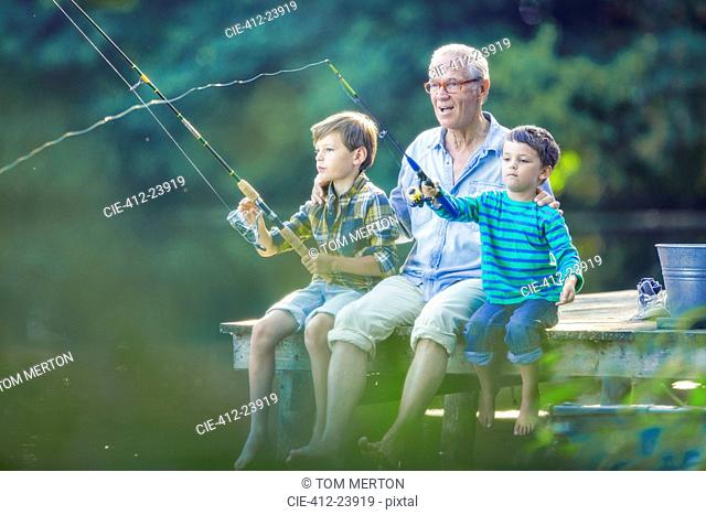 Grandfather and grandsons fishing in lake