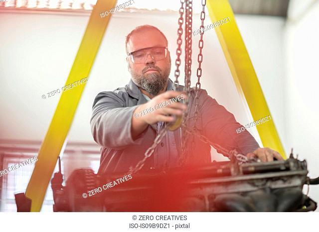 Male car mechanic attaching hoist chain to car engine in repair garage