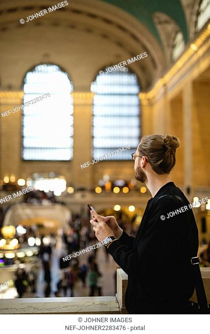 Man holding smartphone, looking away