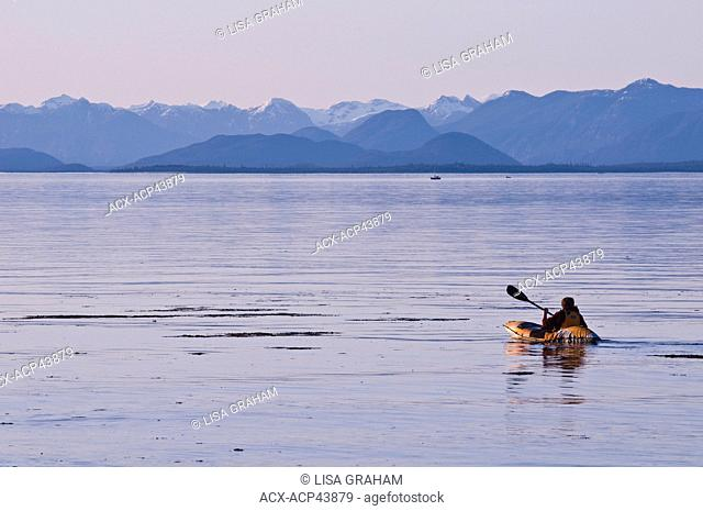 A kayaker at sunset with the westcoast mountain range in the background, Merville, British Columbia, Canada