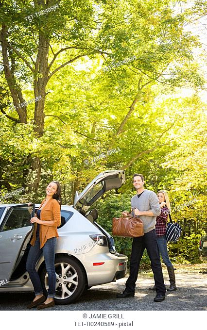 Three friends packing luggage into car