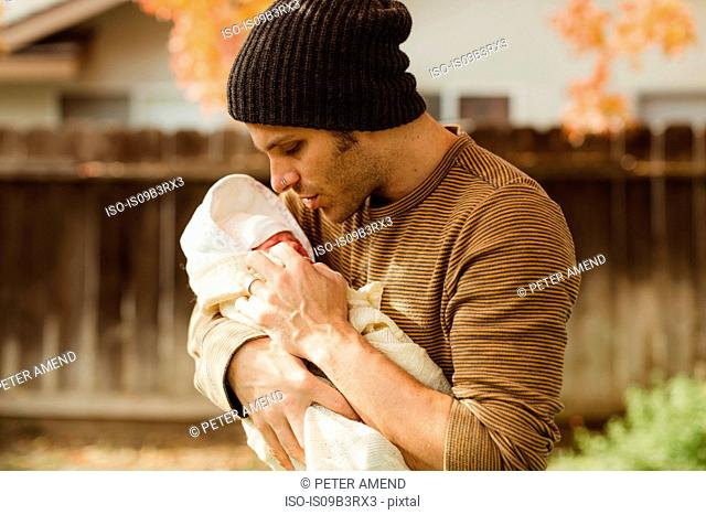 Mid adult man gazing at newborn baby daughter in garden