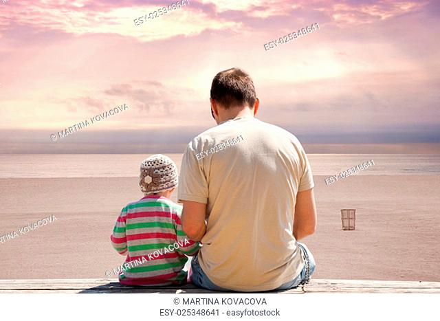 Father and daughter sitting on bench on empty beach at sunset with dramatic atmospheric clouds. Miami Beach Florida, USA