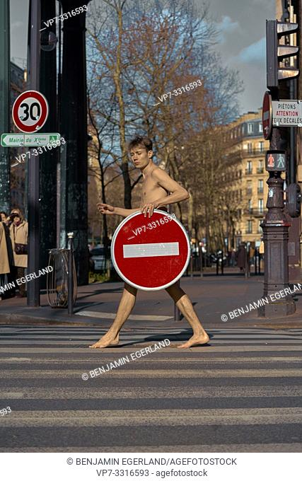 young naked man with prohibition sign walking at street, in Paris, France