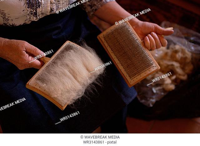 Senior woman using weaving brush at shop