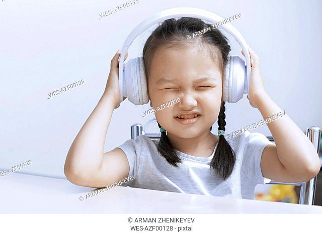 Portrait of little girl listening music with white cordless headphones