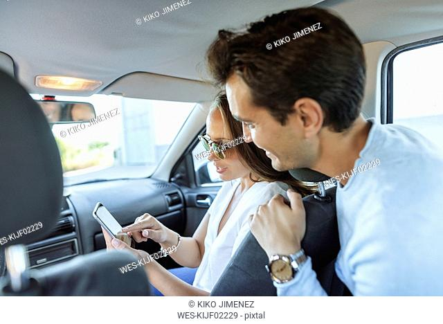 Couple in car with man on back seat and woman with cell phone on front passenger seat