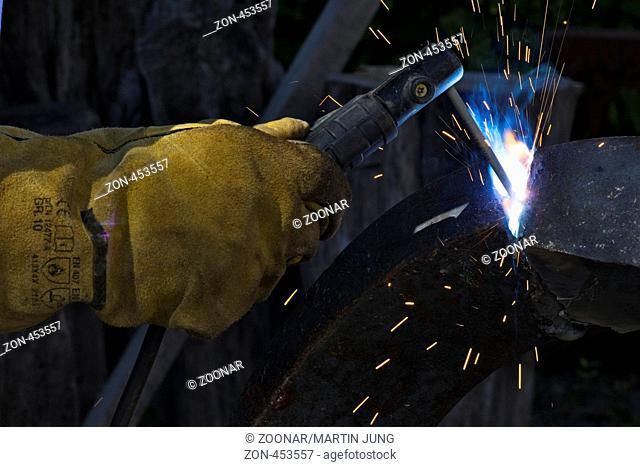 Das Schweißen eines Metallstückes mittels eines Elektroschweißgeräts und einer Schweißelektrode. Man welded metals by means of an electric welder and a welding...