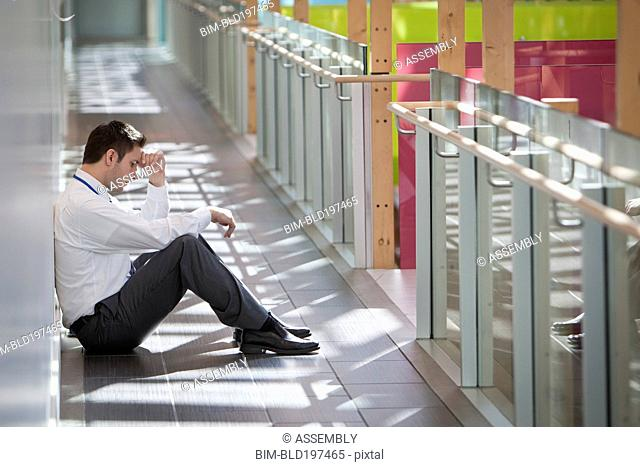 Frustrated businessman sitting on office corridor floor