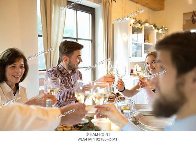 Family clinking glasses at Christmas dinner